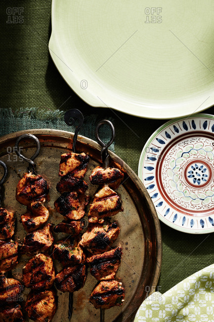 Grilled chicken skewers and plates on table