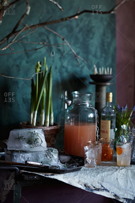 Blocks of ice with juniper and grapefruit cocktails on table