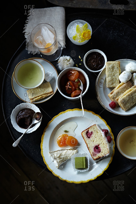 Table set for tea with pastries, fruit and cheese