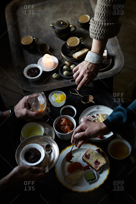Women's hands reaching for items on tea tray