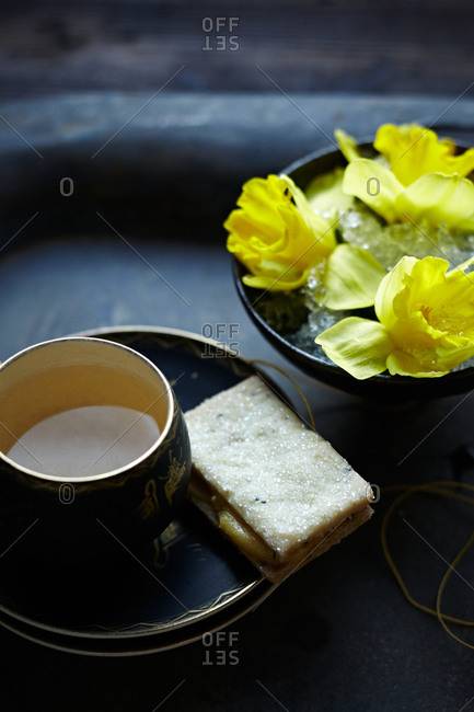 Cup of tea with cookies and daffodils in bowl of ice