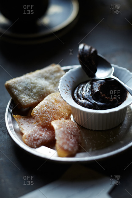 Sugared cookies and citrus rind on plate with dark chocolate mousse