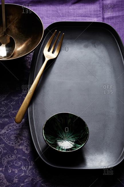Black and gold tableware on purple linens
