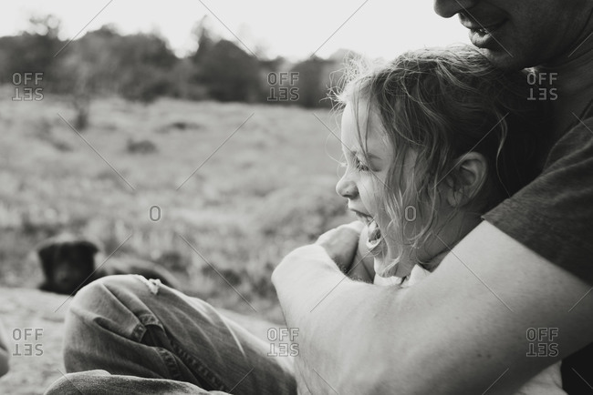 Young girl laughing in father's arms outside