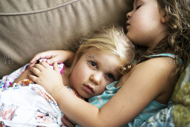 Two little girls cuddling on couch