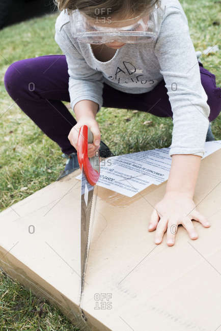 Young girl cutting box with saw
