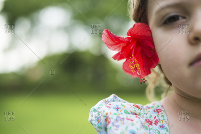 Portrait of girl with hibiscus tucked behind ear