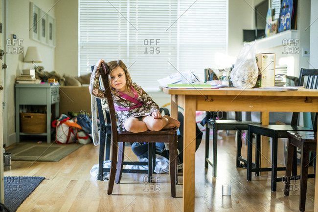 Little girl relaxing in chair while doing homework