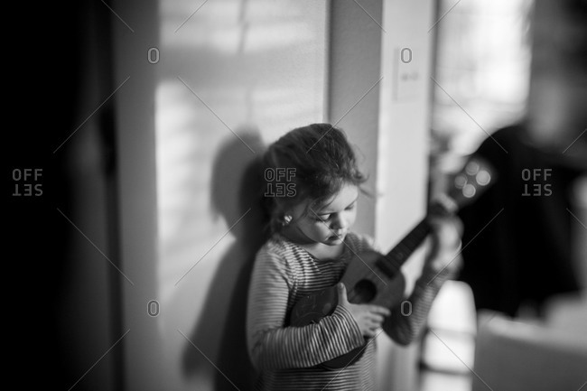 Young girl at home strumming a ukulele