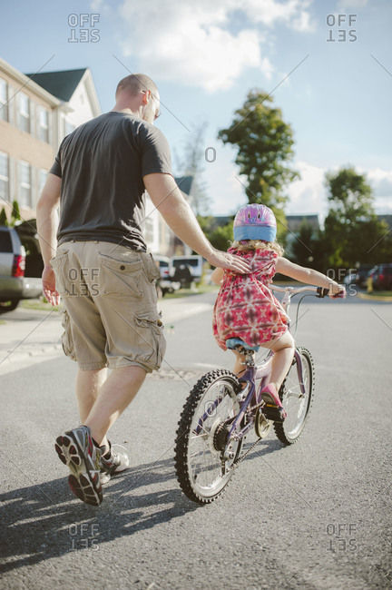 Father helping daughter learn how to ride a bike