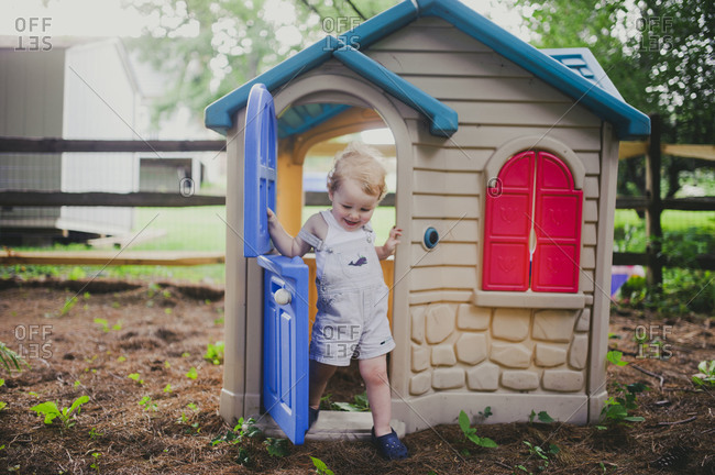 Toddler boy playing in a playhouse in backyard