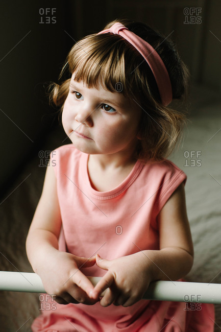 A little girl dressed in pink sits on the edge of her bed