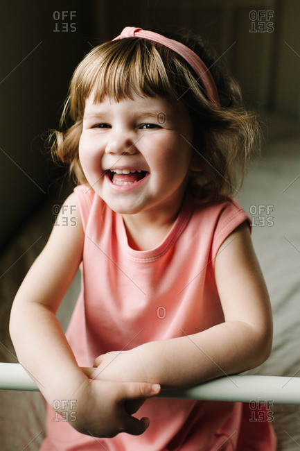 A little girl laughs on the edge of her bed