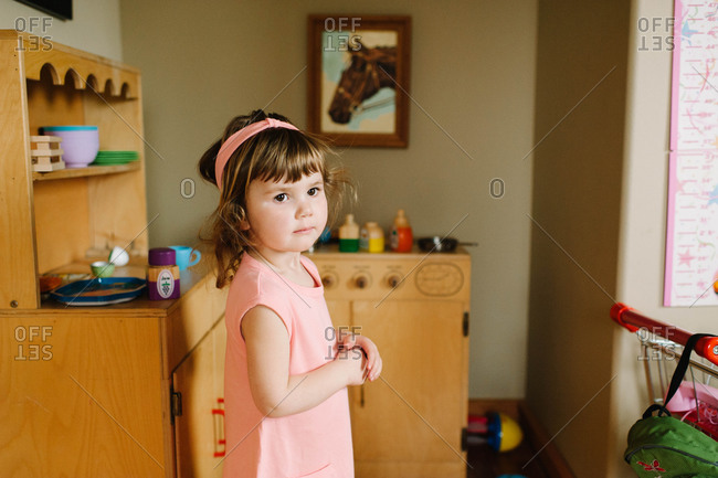 A little girl in a play kitchen