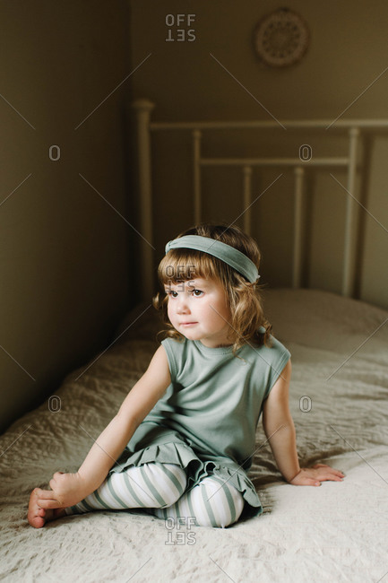 A little girl in light green lounges on her bed