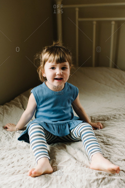 A little girl in a blue dress sits on her bed