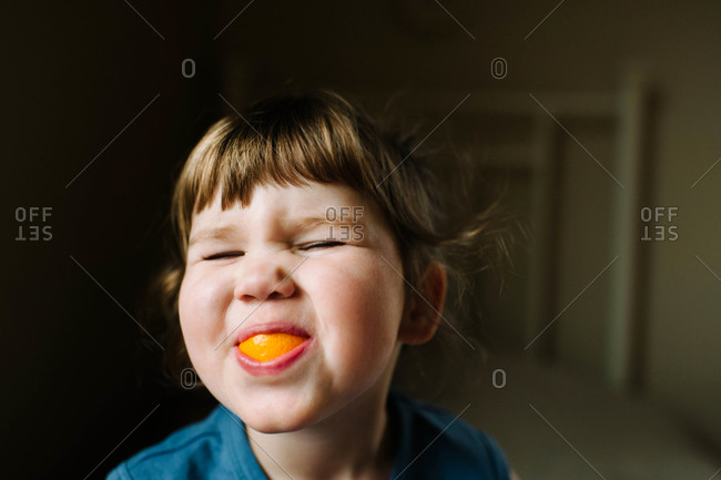 A little girl sucks on an orange wedge