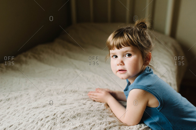A little girl on the edge of her bed