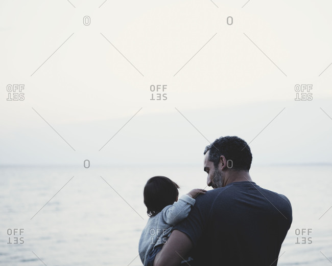 A father smiles at his baby while visiting the shore