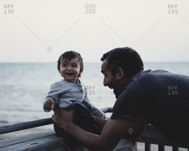 A dad makes his baby laugh while visiting the shore