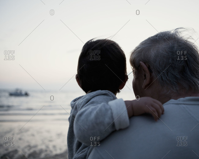 A grandfather holding his grandchild at the beach