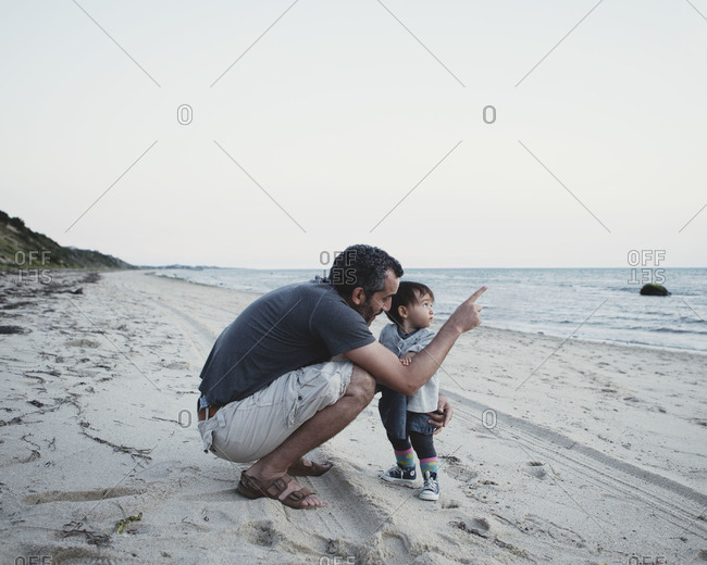 A father shows his baby something in the sky