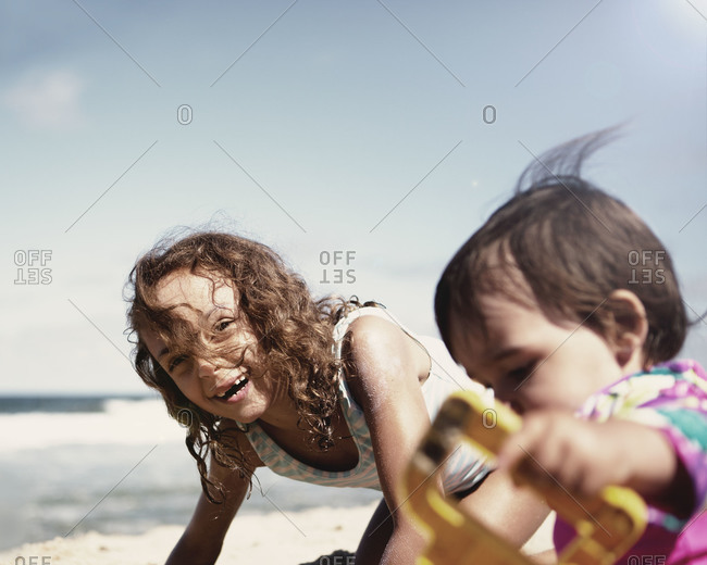 Siblings playing in the sand at beach