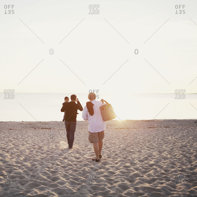 A grandfather, father and daughter walking on the beach