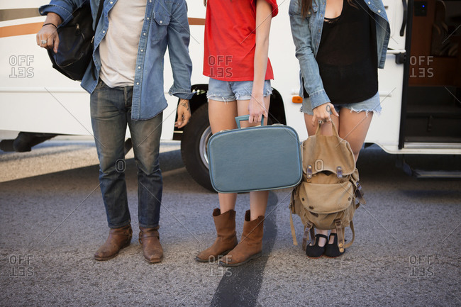 Luggage held by friends in front of RV