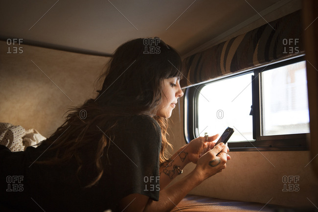 Woman lying on RV bed with phone
