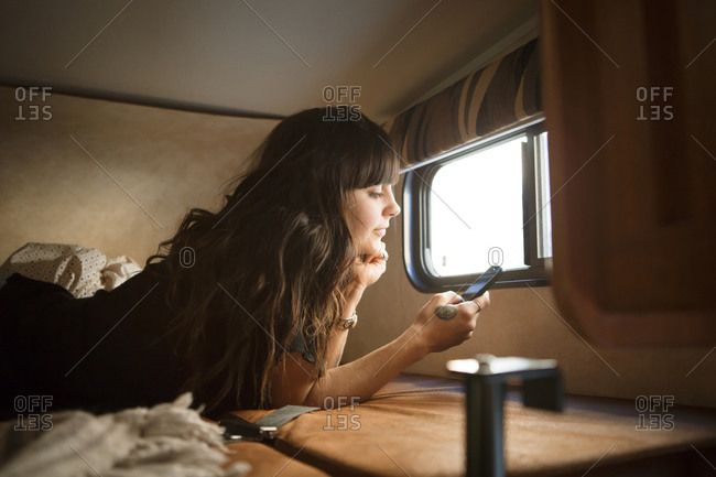 Woman lying on RV bed with cell phone