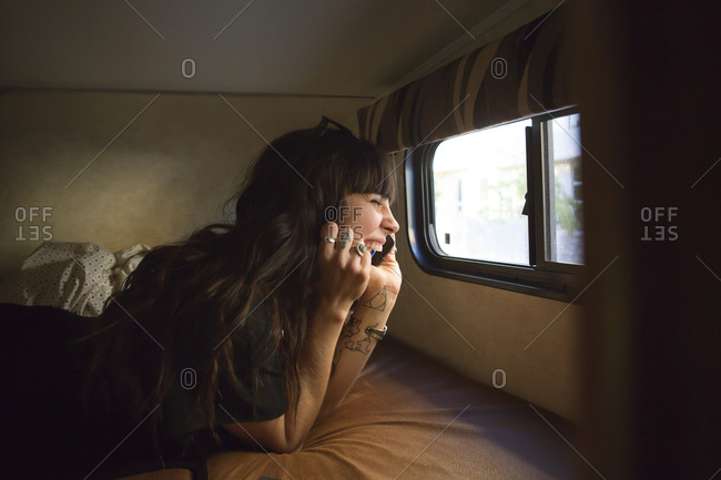 Woman lying on RV bed laughing on phone