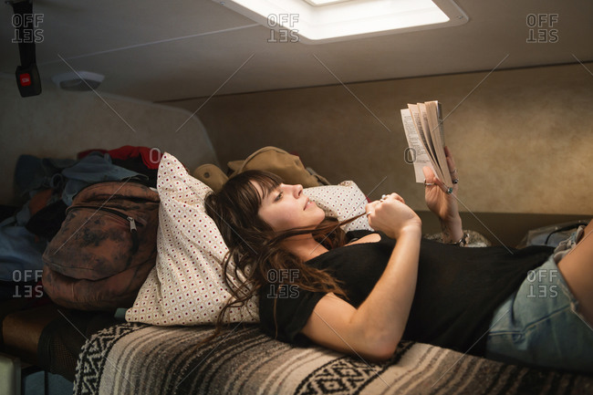 Woman lying on RV bed reading