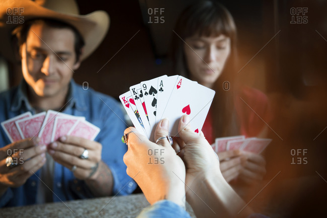 Three friends playing cards at RV table