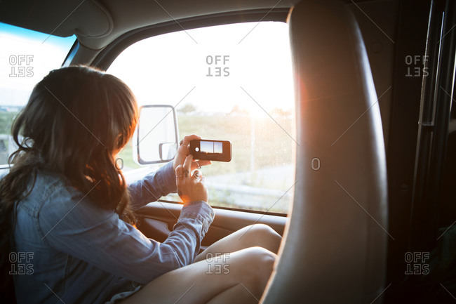 Woman taking sunset pic out RV window