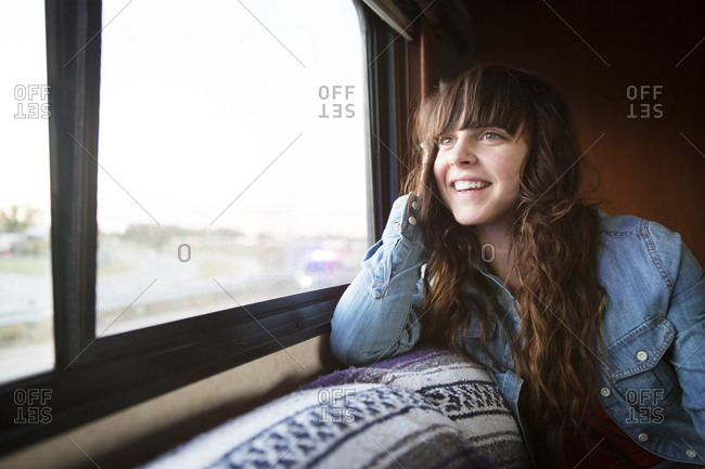 Woman smiling riding in RV looking out window