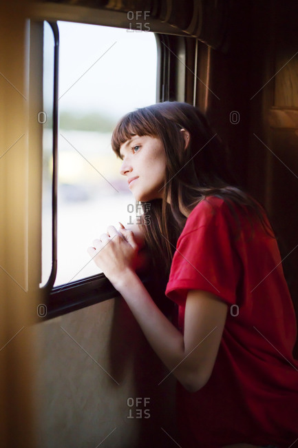 Woman leaning out RV window thinking
