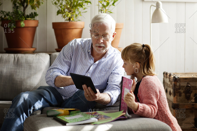A grandfather shows his granddaughter something on his tablet