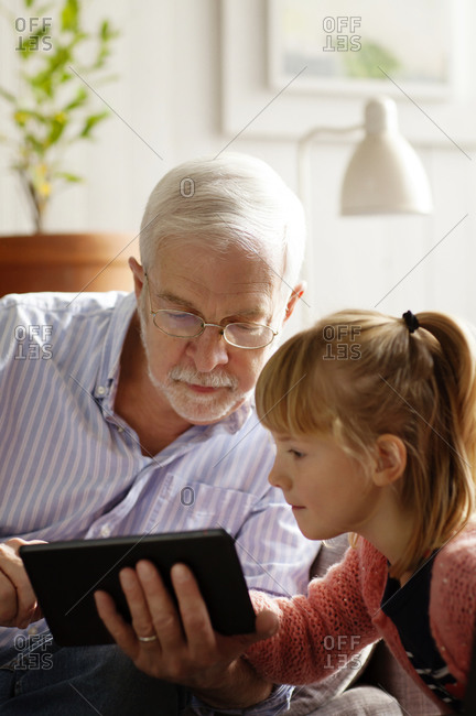 A grandfather and his grandchild look at a table together