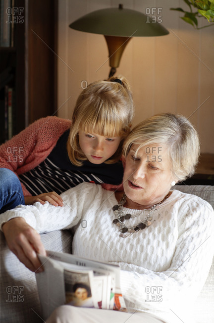 A girl looks over her grandmothers shoulder while she reads a magazine