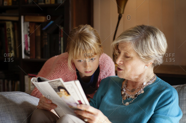 A girl and her grandmother look at a magazine together