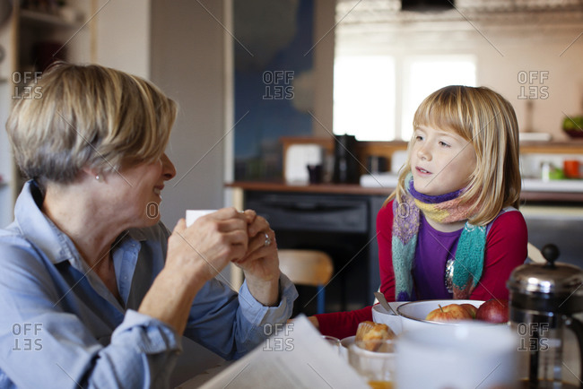 A grandmother and granddaughter chat over breakfast