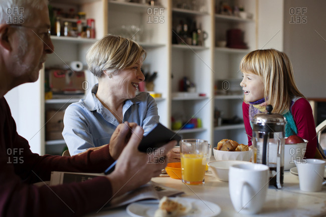 A girl chats with her grandparents over breakfast