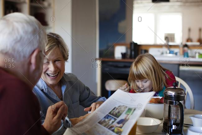 A girl eats breakfast with her grandma and grandpa