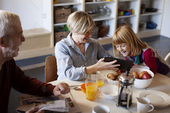 A girl laughs at something on a table with her grandparents