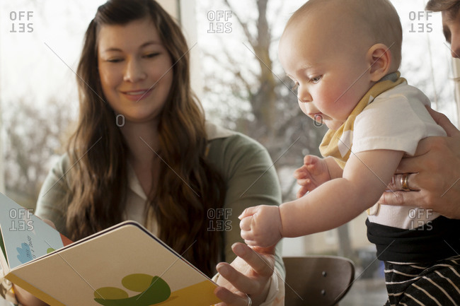 Dad and mom with toddler at table looking at book