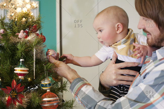 Baby and dad exploring Christmas tree ornaments