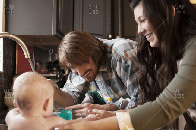 Young parents smiling washing baby in kitchen sink