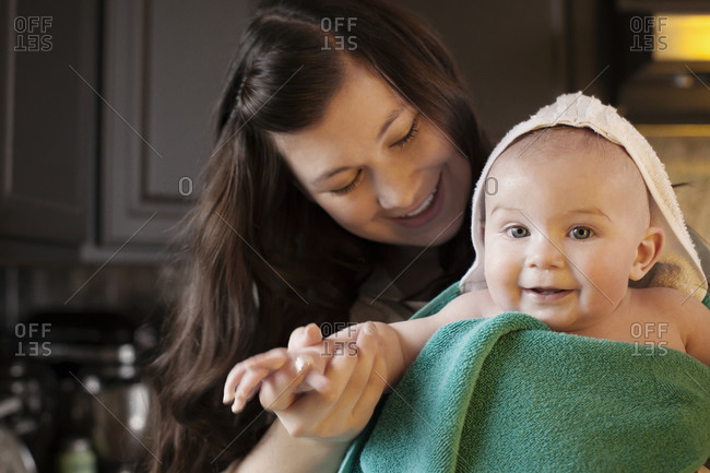 Baby wrapped in towels in mom's arms in kitchen