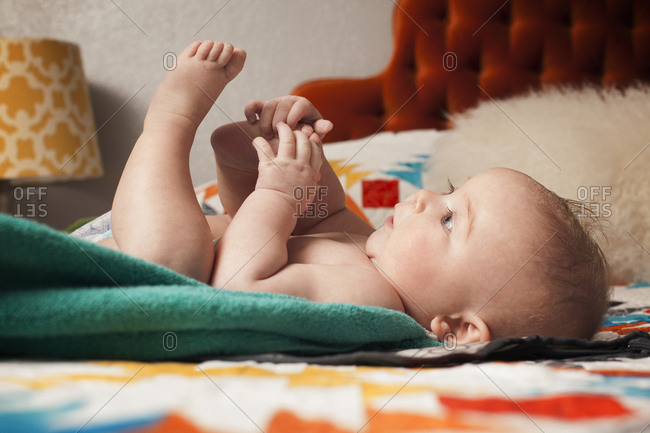 Baby laying on towel on bed playing with feet